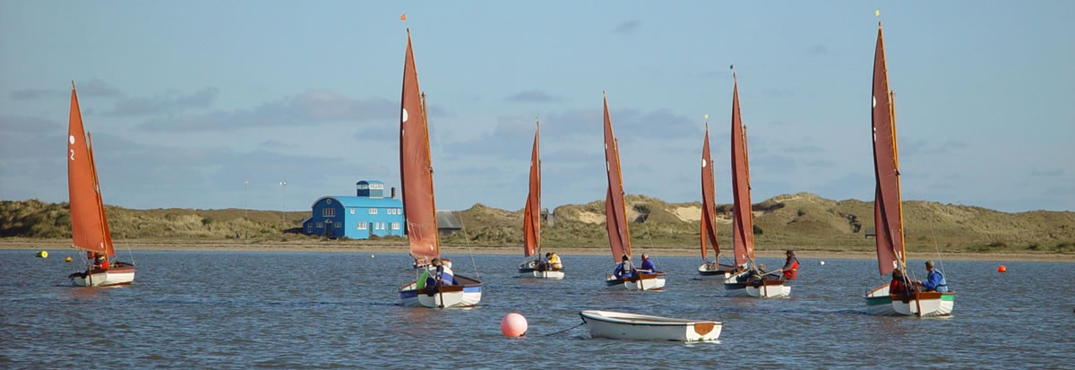 Stiffkey Cockle racing in front of Blakeney Lifeboat house